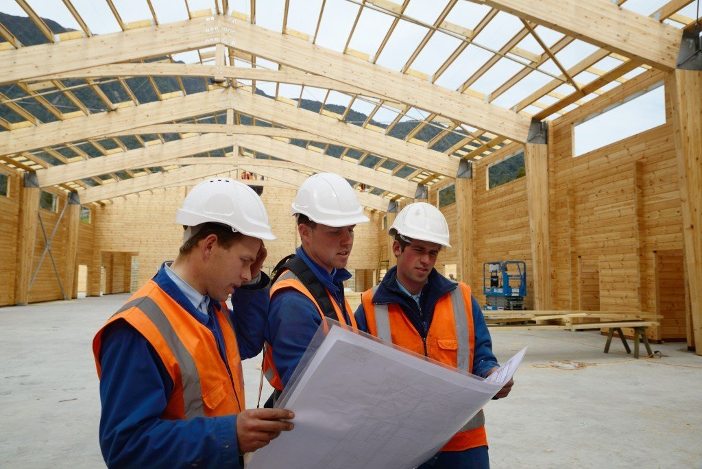 Three builders discuss the plan for a major construction job
